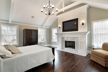 luxury bedroom: Master bedroom in luxury home with marble fireplace