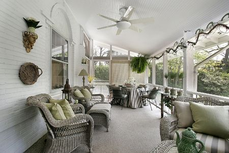 Screen-in porch with wicker furniture and table photo