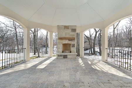 Stone patio with fireplace and wrought iron fence photo