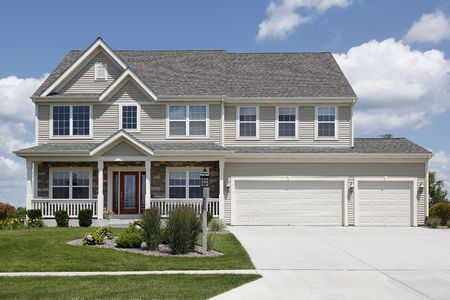 wood lawn: Suburban home with beige siding and double garage Stock Photo