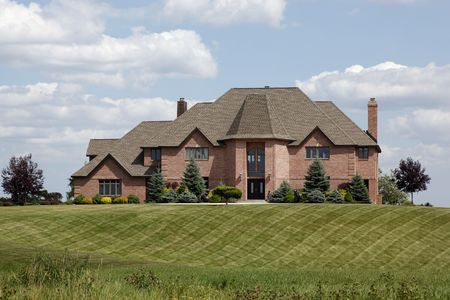 Large luxury brick home with manicured lawn photo