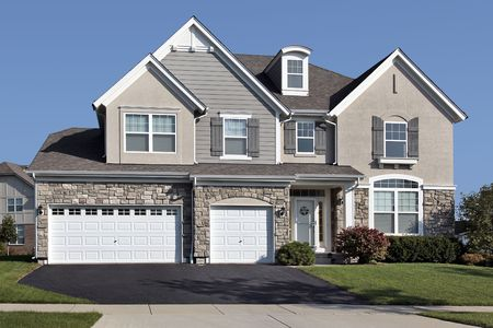 suburbs: Home in suburbs with three car stone garage Stock Photo