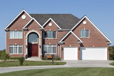 Brick home in suburbs with arched entrance Imagens