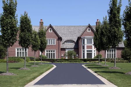 Large brick home in suburbs with row of trees photo
