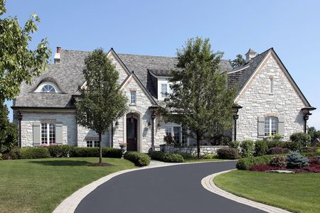 Large luxury stone home with circular driveway