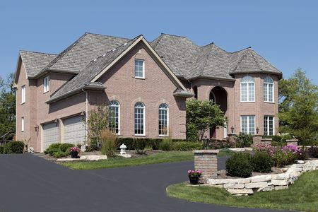 Luxury brick home in suburbs with arched entry photo