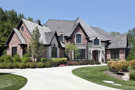 Large brick home in suburbs with circular driveway Stock Photo