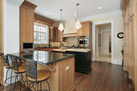 Kitchen in luxury home with granite and black island photo