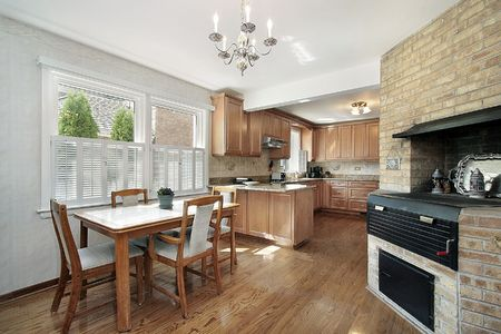 Wood cabinetry kitchen in luxury home with brick wall photo