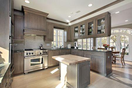 cucina moderna: Cucina nella casa ristrutturata con mobili in legno e isola Archivio Fotografico