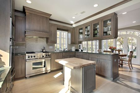 Kitchen in remodeled home with wood cabinetry and island photo