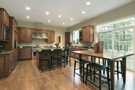 Luxury kitchen with wood cabinets and eating area photo