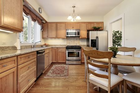 Kitchen and table in suburban home with wood paneling