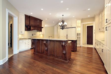 Kitchen in luxury home with wood paneling and marble island photo