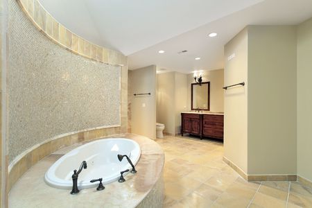 Master bath in new construction home with marble tub photo