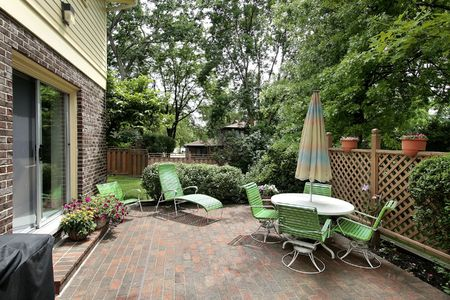 Suburban home with brick patio and green furniture photo