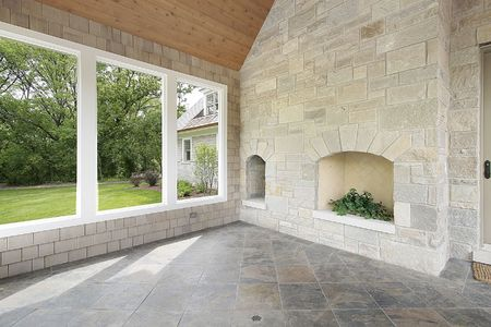 Stone porch in new construction home with fireplace photo
