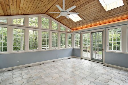 Sunroom in suburban home with wall of windows