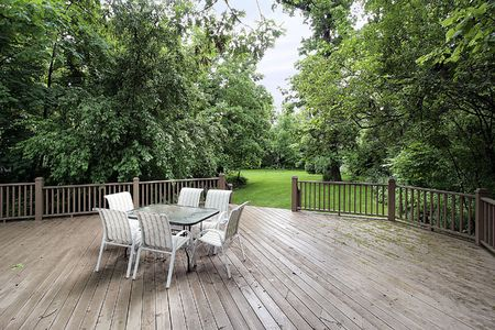 Large wooden deck with table and chairs leading to backyard Stock Photo