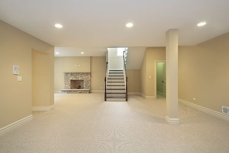 home furnishing: Basement in new construction home with stone fireplace