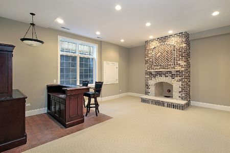 Basement in new construction home with brick fireplace photo