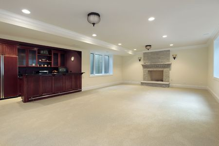 Basement in new construction home with bar and fireplace photo