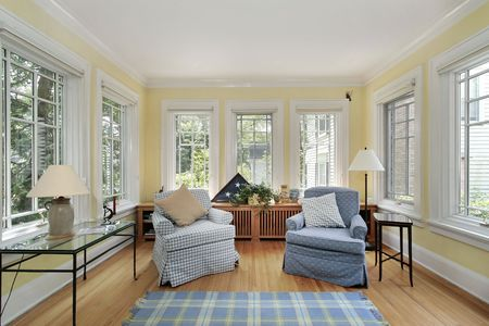 Sun room in suburban home with wall of windows