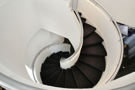 Spiral staircase with white walls in luxury home photo