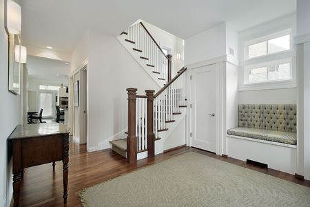 entryway: Foyer in older suburban home with white stair railing Stock Photo