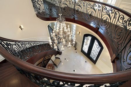 home lighting: Curved stairway leading down into foyer in luxury home