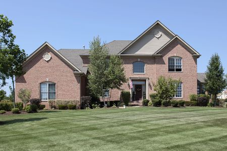 Luxury brick home in suburbs with manicured lawn photo