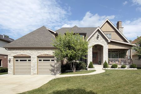 Luxury stone home with arched entry and front porch photo