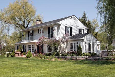 White suburban home with second floor balcony