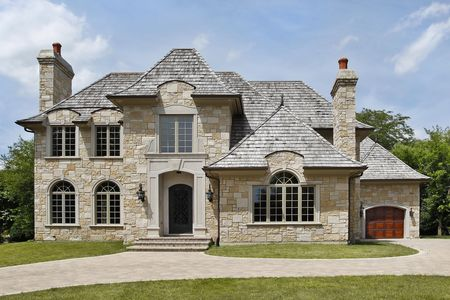 custom home: Luxury stone home with arched entry way Stock Photo