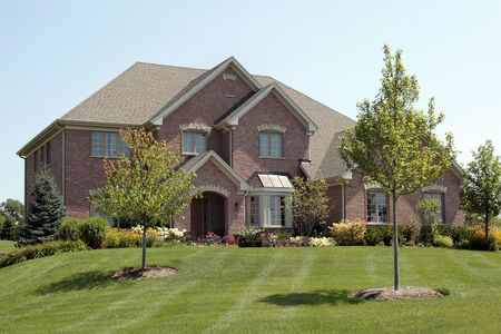 lawn: Luxury brick home in suburbs with arched entry Stock Photo
