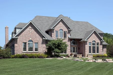Luxury brick home in suburbs with stone landscaping photo