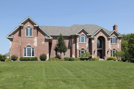 single dwelling: Large brick home in suburbs with arched entry Stock Photo