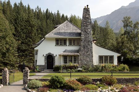 Country home with large brick chimney and mountain backdrop photo