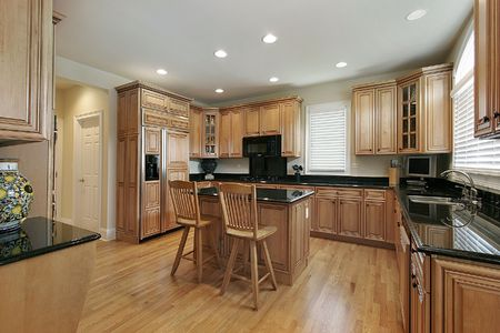 Large kitchen with wooden cabinetry and island photo