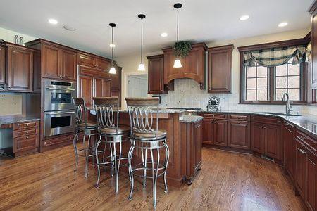 lighting fixtures: Kitchen in new construction home with cherry wood cabinetry
