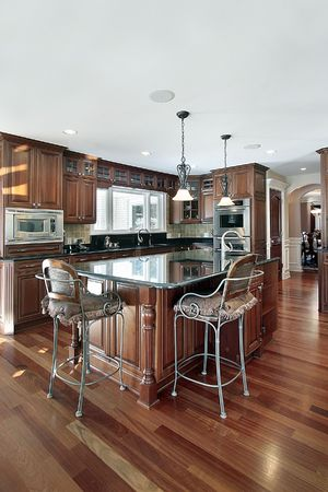 modern dining room: Kitchen in luxury home with cherry wood cabinetry Stock Photo