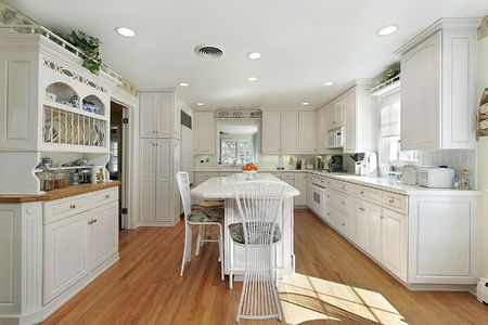 modern dining room: Kitchen in suburban home with white island Stock Photo