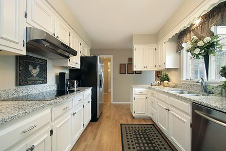 cabinetry: Kitchen in suburban home with white cabinetry Stock Photo