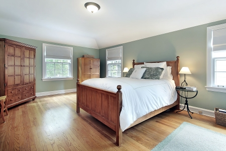 bedroom design: Master bedroom in suburban home with oak wood furniture