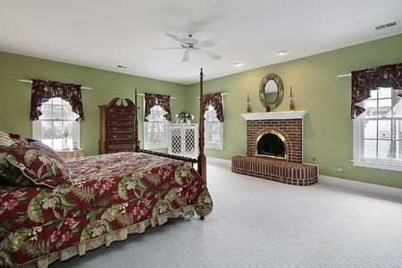 Master bedroom in suburban home with brick fireplace photo