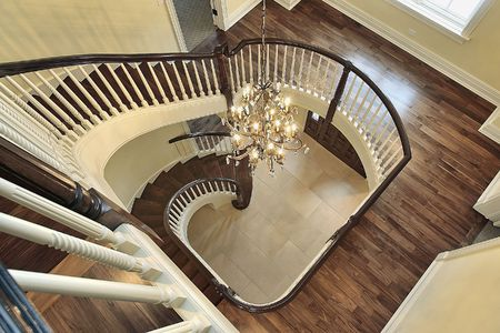 Spiral staircase with foyer view in new luxury construction home photo