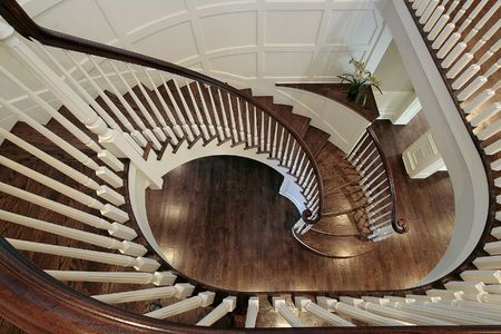 Spiral staircase in luxury home with wood railing photo