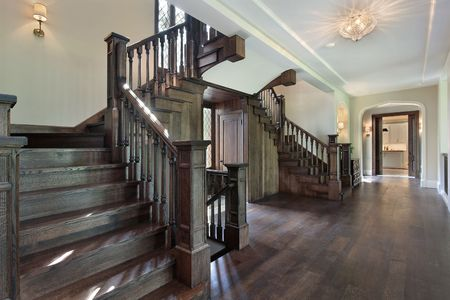 entryway: Foyer in new construction home with dark wood stairway