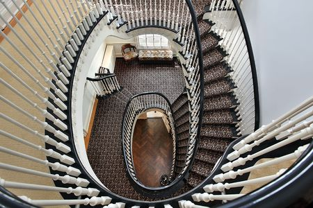 Spiral staircase in luxury home with black railing photo