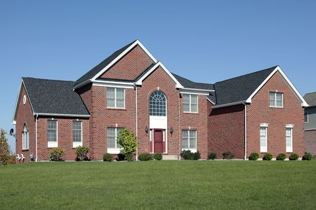 Large brick home with red door and curved window Stock Photo - 6739142